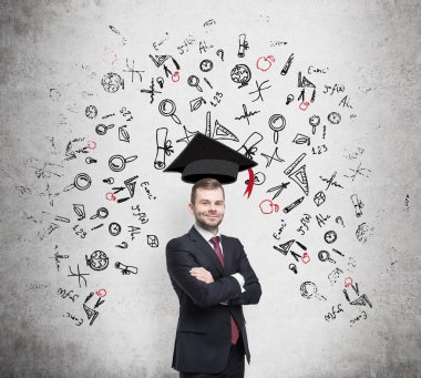 Young handsome businessman is thinking about education at business school. Drawn business icons over the concrete wall. Graduation hat.