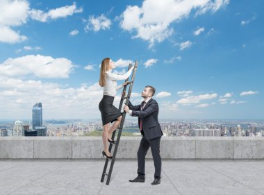 Businessman is holding a ladder for the business lady. The concept of the teamwork. On the roof terrace in the Manhattan, New York. Falling dollars from the sky.