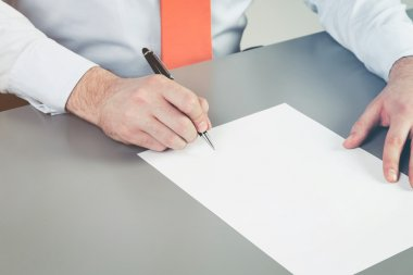 Close up of businessman's hand intending to write a document, petition or claim. A concept of drafting documentation process. Signing the legal document.