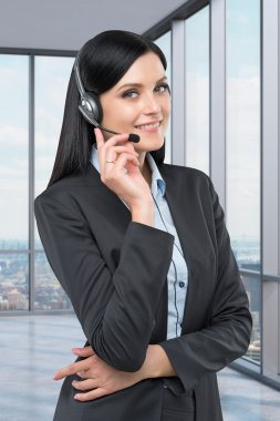Portrait of brunette support phone operator with the headset. New York panoramic office on the background.