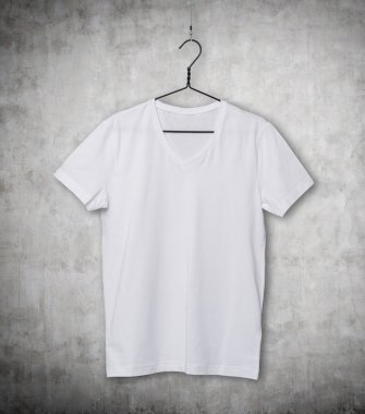 Close-up of the white t-shirt on the clothes hanger. Concrete background.
