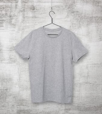 Close-up of the grey t-shirt on the clothes hanger. Concrete background.