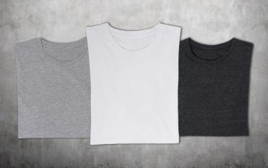 Close-up of the three t-shirts (black, white and grey). Concrete background.