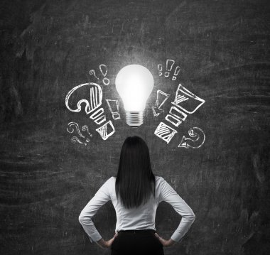Rear view of the brunette woman in formal clothes. Drawn exclamation, question marks and a light bulb as a symbol of the new business idea.