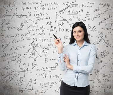 Portrait of smiling woman who points out complicated math calculations. Math formulas are written on the concrete wall.