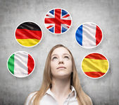 Photo Beautiful lady is surrounded by bubbles with european countries flags (Italian, German, Great Britain, French, Spanish). Learning of foreign languages concept. Concrete background.
