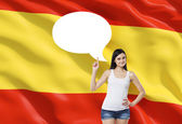 Beautiful woman is pointing out the empty thought bubble. Spanish flag as a background.