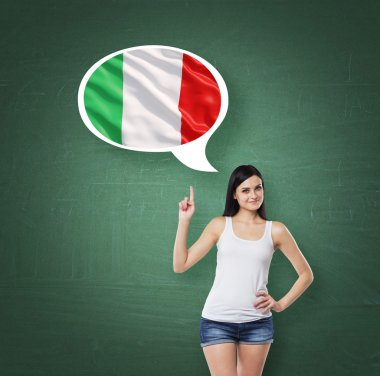 Beautiful woman is pointing out the thought bubble with Italian flag. Green chalk board background.