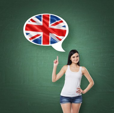 Beautiful woman is pointing out the thought bubble with Great Britain flag. Green chalk board background.