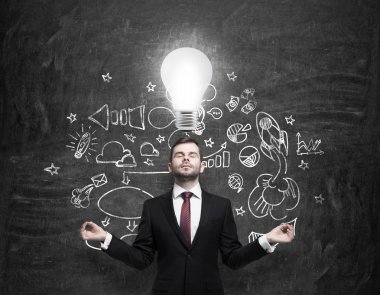 Meditative young businessman is looking for new business ideas. Drawn business icons on the black chalk board and a light bulb as a concept of new idea.