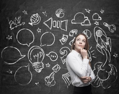 Young beautiful lady is thinking about optimisation of the marketing business process. Social media icons are drawn on the black chalk board.