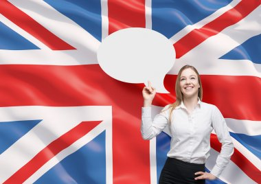 Beautiful woman is pointing out the empty thought bubble. Great Britain flag as a background.