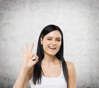 Brunette woman shows ok sign. Concrete background. stock vector