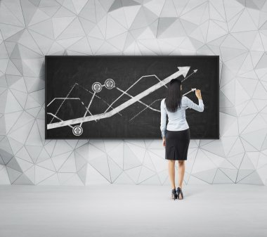 Rear view of full-length brunette woman who is presenting growing line graph on the black board.