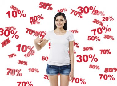 Brunette in denim shorts and white tank top pointing out to the chest. The concept of the discounts and sale. 10% 20% 30% 50% 70% symbols.