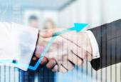 A handshake over growing arrow and business couple in blur on the background.