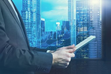 Close-up of side view of a businessman who is browsing on his tablet. Panoramic Manhattan evening view, New York. Forex chart is over the cityscape. Toning filter.