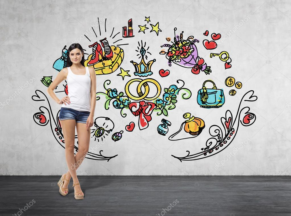 Full length portrait of a brunette woman who is in a white tank top and blue denim shorts. She is dreaming about sopping. Colourful shopping icons are drawn on the concrete wall.