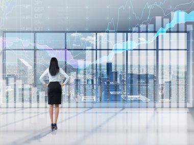 Full-length of brunette lady who is looking through the window. A modern panoramic office with New York city view and forex chart. A concept of the asset management.