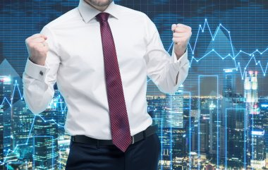 Closeup of successful portfolio manager in white shirt with pumped fists. A concept of the celebrating of success. Forex chart and evening New York view on the background.