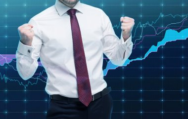 Closeup of successful portfolio manager in white shirt with pumped fists. A concept of the celebrating of success. Forex chart on the background.