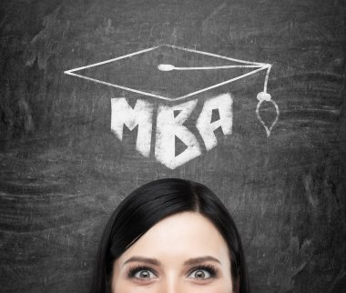 A head of young brunette lady who is thinking about MBA degree. Drawn a graduation hat on the black chalkboard background .