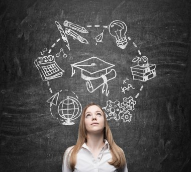 Young beautiful lady thinks about studying and graduation. Educational icons are drawn on the black chalkboard.