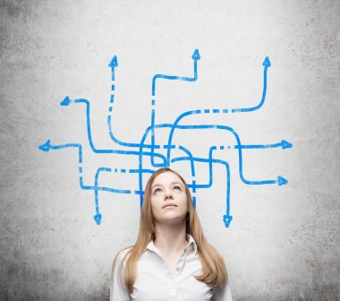 A beautiful young lady is pondering about possible solutions of the complicated problem. Many blue arrows with different directions are drawn around her head. Concrete wall as a background.