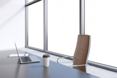 A workplace in a modern panoramic office with copy space in the windows. A grey table, brown leather chair. Laptop, writing pad and a cap of coffee are on the table. Office interior. 3D rendering.