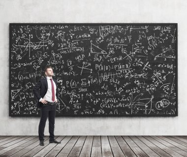 Side view of a confident young man who stands in front of black chalkboard which is full of math formulas. A concept of Analyst at investment bank.
