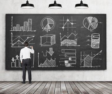 Young businessman or student of finance or management programme is drawing some charts or graphs on the black chalkboard. Rear view of the model. Wooden floor and three ceiling lights in the room.