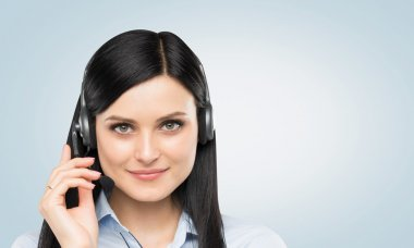 Front view of the smiling brunette support phone operator with headset. Light blue background.