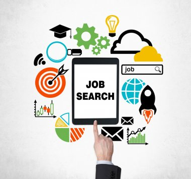 A finger is pushing the button on the tablet to find new job vacancies. Looking for a job in the Internet. The concept of searching job and technology. Internship and graduate programmes.