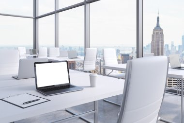 Workplaces in a modern corner panoramic office in Manhattan, New York City. White tables and white chairs. A laptop with a white screen, notepad and a coffee cup. 3D rendering.
