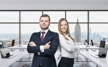 Couple of young managers are standing in the modern panoramic office. New York, Manhattan panoramic view.