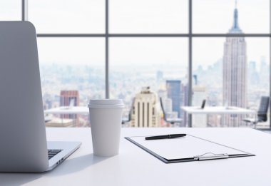A workplace in a modern panoramic office in Manhattan, New York City. A laptop, notepad and a coffee cup are on the white table. 3D rendering.