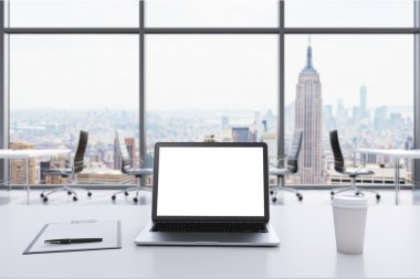 A workplace in a modern panoramic office in Manhattan, New York. A laptop with white screen, notepad and a coffee cup are on the white table. Open space. 3D rendering.
