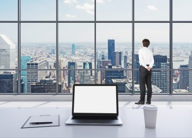 A dressed person in formal clothes is standing in modern panoramic office and looking at New York. A laptop with white screen, a writing pad and a cup of coffee are on the white table.