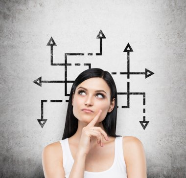 A beautiful brunette woman who is pondering about possible solutions of the complicated problem. Many arrows with different directions are drawn around her head. Concrete wall on background.