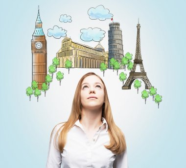 A beautiful woman is looking up by dreaming about the visiting of the most famous European cities. The concept of tourism and sightseeing. Light blue background.