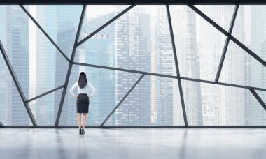Rear view of a full length lady in formal clothes who is looking out the window in a modern panoramic open space in Singapore. The concept of highly professional financial or legal services.