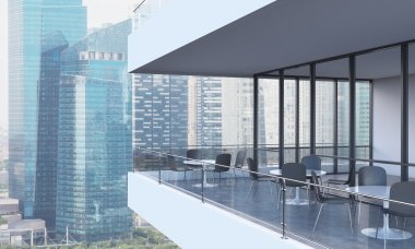 A woman is looking at Singapore standing on the terrace in a modern skyscraper with panoramic windows.