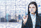 A brunette woman is writing down math formulas in the glass screen. Modern panoramic office with New York view in blur on the background.