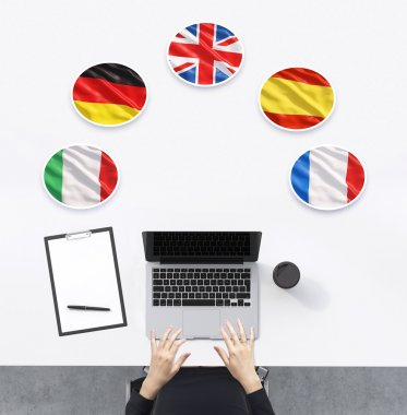 Top view of the working place with woman's hands. A laptop, notepad and a cup of coffee are on the table. Italian, German, United Kingdom, Spanish and French flags in the bubbles.