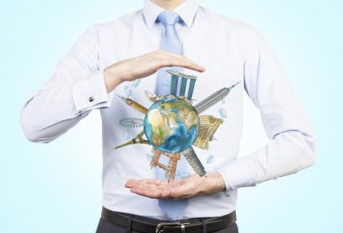 A man holds between his hands the globe with sketched famous places. Light blue background. Elements of this image furnished by NASA.