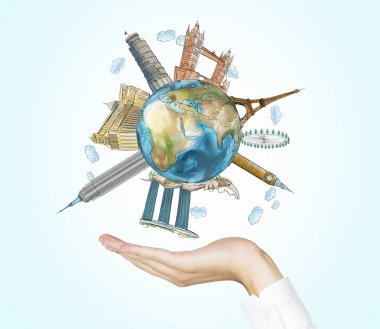 A hand holds a globe with sketched the most famous places in the world. A concept of tourism and sightseeing. Light blue background. Elements of this image furnished by NASA.