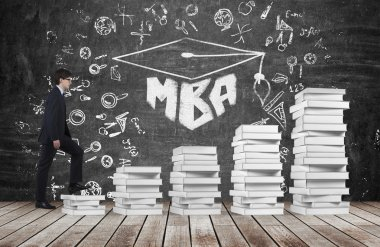A man is going up using a stairs which are made of white books to reach graduation hat. The written word MBA is drawn on the black chalkboard which symbolises a professional business education.