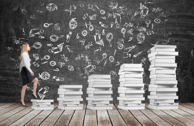 A woman is going up using a stairs which are made of white books. Educational icons are drawn on the black chalkboard. Wooden floor.