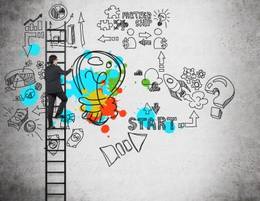 A businessman on the ladder is drawing business management icons and a colourful lightbulb on the concrete wall. The concept of the brainstorm or a start up.