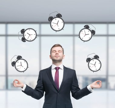 Meditative businessman is pondering about time management in the modern panoramic office. The person in formal suit is surrounded by alarm clocks. A concept of time management and deadlines.